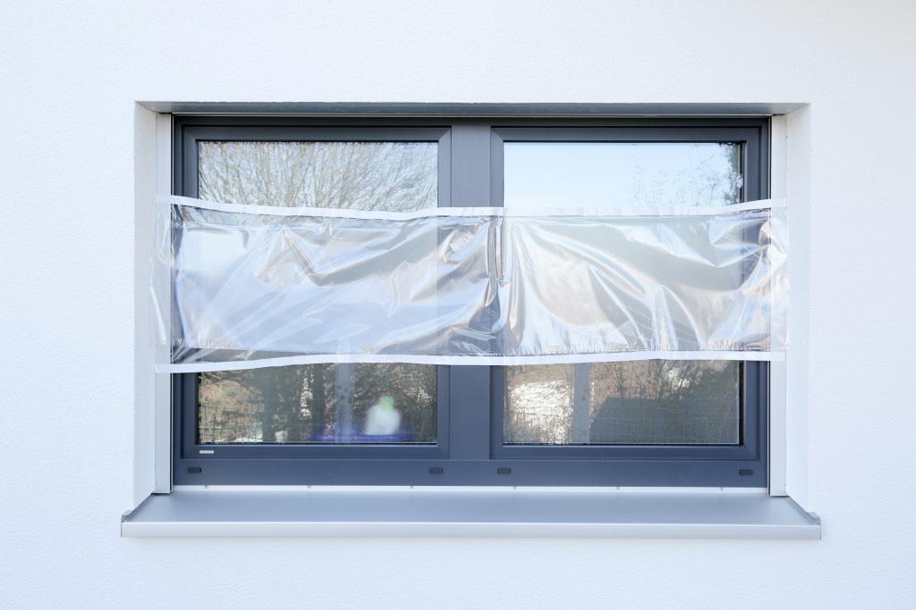 Ein Fenster ist zu einen Drittel mit Malerfolie abgeklebt