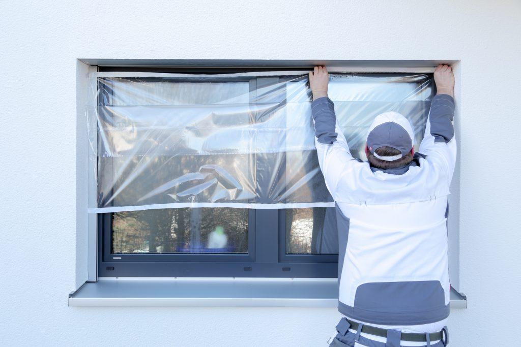 Ein Maler klebt mit Folie von Klauss-Klebeband ein Fenster ab