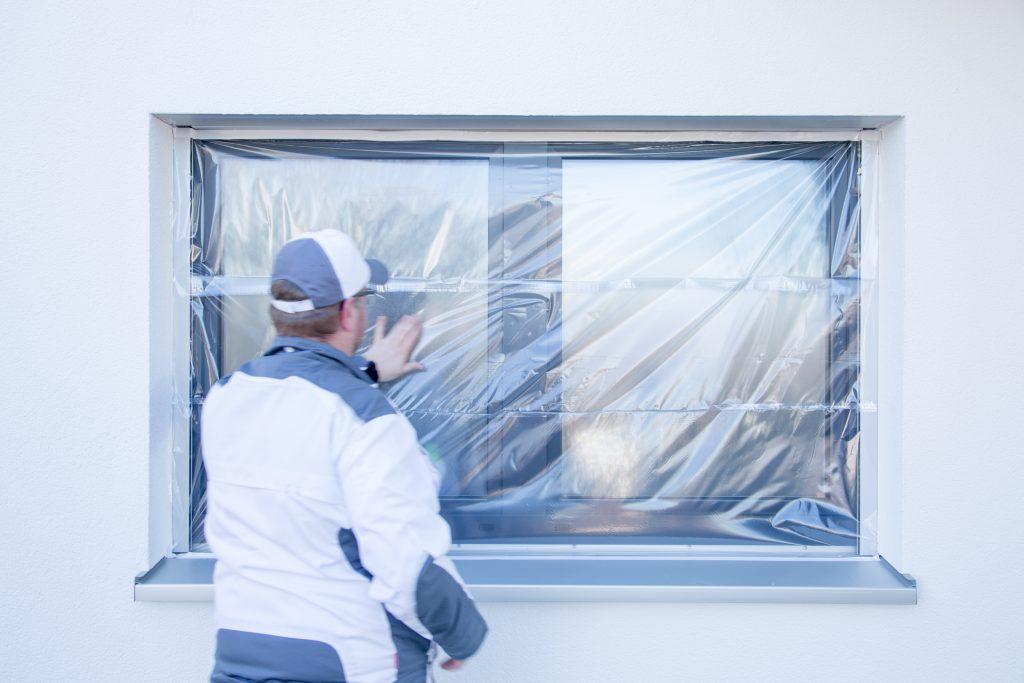 Ein Maler klebt mit der ProTaper Edition von Klauss-Klebeband einen Fensterrahmen ab